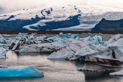Big ice blocks, melting and cracking from the main glacier at Jökulsárlón at blue hour. Jökulsárlón is a large glacial lake in southern part of Vatnajökull National Park, Iceland