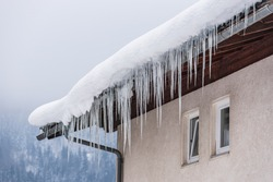 Big icicles and snow hanging over the rain gutter on a roof of a traditional wooden house in the mountains in winter could be dangerous. Trees at the background.