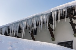 Big icicles and snow hanging over the rain gutter on a roof of a traditional wooden house in the mountains in winter could be dangerous. Blue sky at the background.