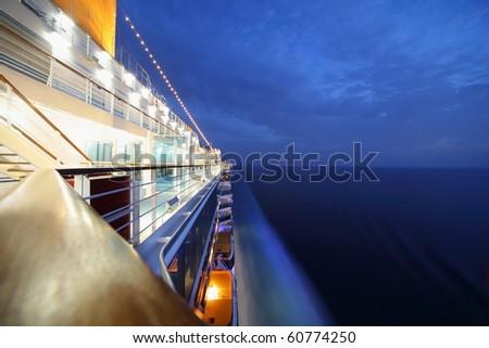 big illuminated cruise ship riding in evening. wide angle.