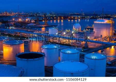 Big Industrial estate  a lot of oil tanks in a refinery with treatment pond at industrial plants twilight time , copy space