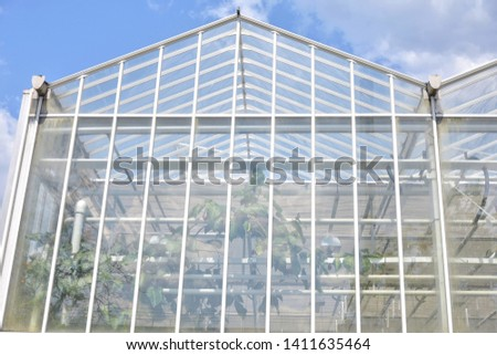 Big industrial greenhouse from glass panels on blue sky background. Agriculture glasshouse for growing plants. Transparent green house for growing organic vegetables. Cultivating agricultural plant #1411635464