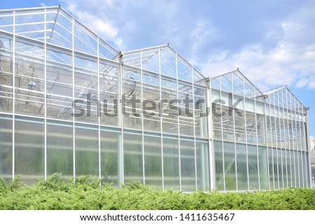 Big industrial greenhouse from glass panels on blue sky background. Agriculture glasshouse for growing plants. Transparent green house for growing organic vegetables. Cultivating agricultural plant #1411635467