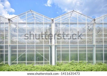 Big industrial greenhouse from glass panels on blue sky background. Agriculture glasshouse for growing plants. Transparent green house for growing organic vegetables. Cultivating agricultural plant
