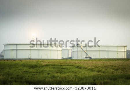 Big Industrial oil tanks - Natural Gas storage tanks - Oil Refinery factory at twilight , petrochemical plant , Petroleum , Chemical Industry