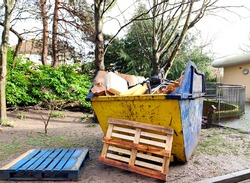 Big industrial rubbish skip in garden. Space to add text in front or side of the empty metal bin. Great for office renovation, house clearance, building site, recycle and waste management concept.