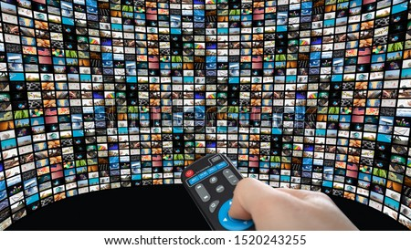 Big interactive TV with many smart channels, man's hand with remote control.