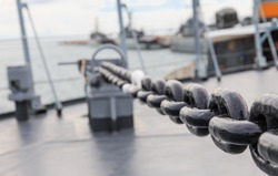 big iron chain of anchor on board navy ship in close up