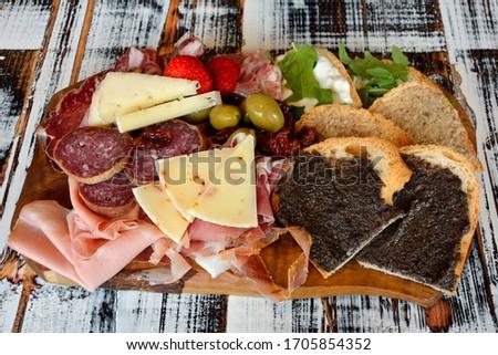 Big Italian cutting board with crostini, sausage, ham, olives and strawberries in San Marino Foto stock ©