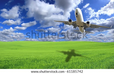 BIg jet airplane flying above green field