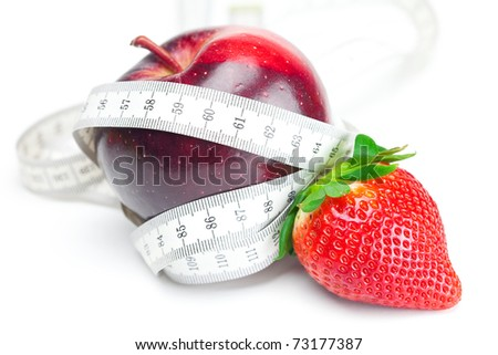 big juicy red ripe strawberries,apple and measure tape isolated on white