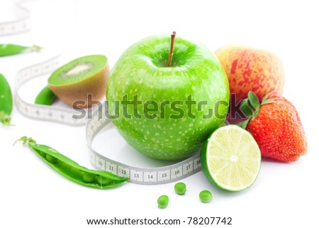 big juicy red ripe strawberries,apple,lime,peas,peach,kiwi  and measure tape isolated on white
