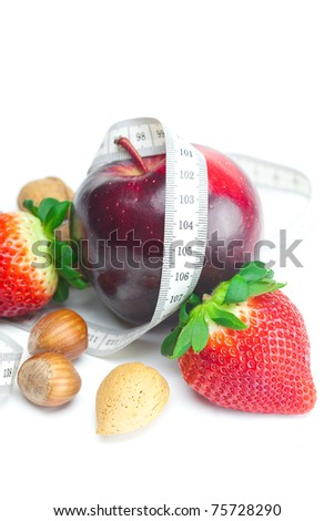 big juicy red ripe strawberries,apple,nuts and measure tape isolated on white