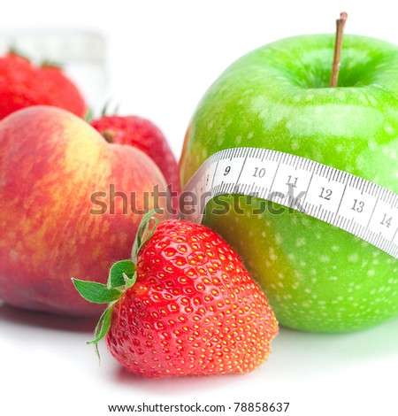 big juicy red ripe strawberries,apple,peas,peach and measure tape isolated on white