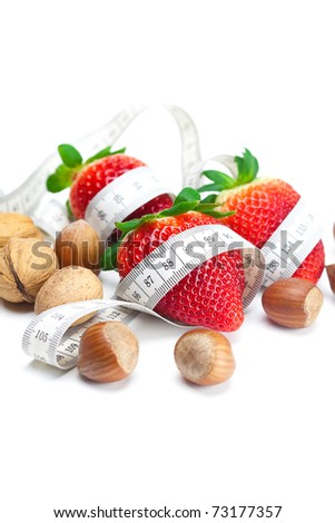 big juicy red ripe strawberries,nuts and measure tape isolated on white