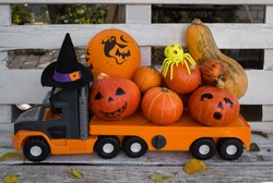 big kids toy car - truck loaded with many beautiful orange pumpkins. Preparing for the scary Halloween holiday. Festive street decoration. autumn harvest of vegetables. delivery of products
