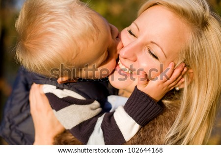 Big kiss for mom, cute young boy kissing his mother.