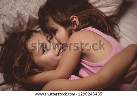 Two girls kissing in the bed