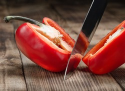 Big kitchen knife cut a bell pepper on two parts close up on wooden table