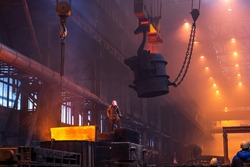 Big ladle on crane before melting in foundry workshop. Smelting of multi-ton cast iron parts. Metallurgical plant or Steel Mill