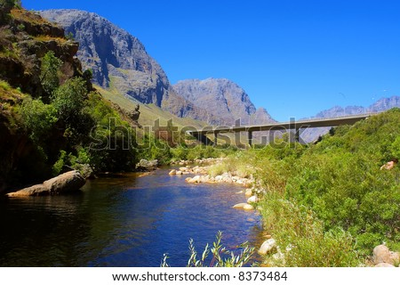 Big lake and highway bridge in awesome mountains. Shot in the Kromrivier - Du Toitskloof Nature Reserve, near Paarl, Western Cape, South Africa.