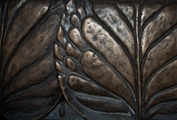 Big leaves close-up macro dark bronze metal relief background. Vintage water lily sculpture foliage art