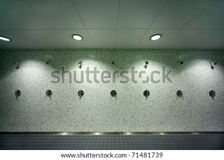 big, light, empty public shower room, green tile on walls, gray floor