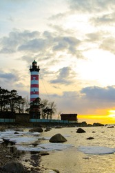 Big lighthouse on the beach at sunset