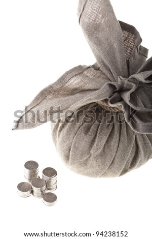 Big linen bag full of money tied by rope and one polish zloty coin stacks. Money and savings concept on white background.