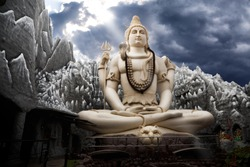 Big Lord Shiva statue sitting in lotus with trident in his hand and cobra near by. Dramatic sky at background with ray on Shiva. Bangalore, India