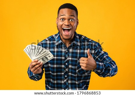 Big Luck And Profit. Excited African Guy Holding Money Gesturing Thumbs-Up Posing Over Yellow Background. Studio Shot Сток-фото ©