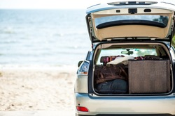 Big luggage, suitcase, bag inside the trunk of cream, silver car jeep on the beach