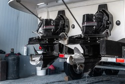 Big luxury cabin motorboat cruiser yacht engine at trailer ramp from storage boat hangar garage. Ship service, cleaning, repair or maintenance concept. Luxury fishing leisure recreation lifestyle
