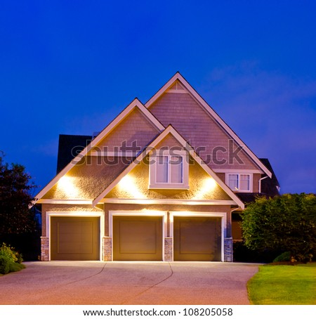 Big luxury house with the triple garage doors at dusk, night in suburbs of Vancouver, Canada
