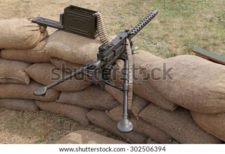 big machine gun with bullets over the sandbags in the trench