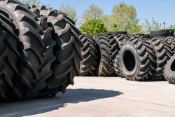 Big machines tires stack background. Industrial tires outside for sale