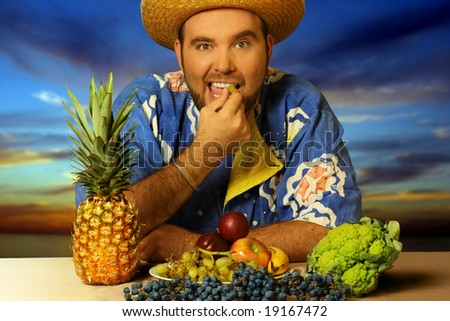 big man eating fruit by the beach