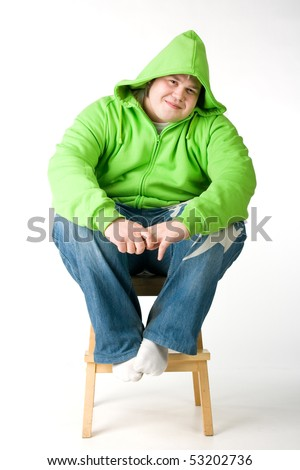 Big man in a green jacket with hood sitting on a chiar