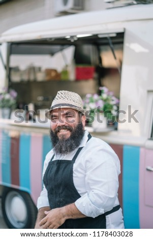 Big man with beard and hat serves food on food track #1178403028