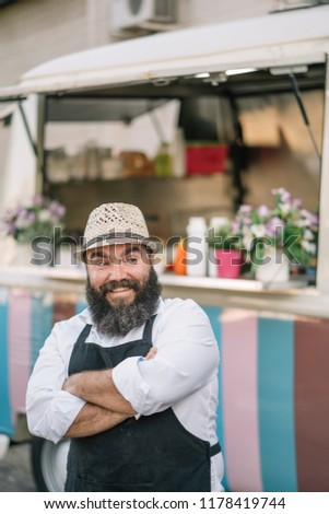 Big man with beard and hat serves food on food track #1178419744