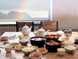 Big meal of korean food for family group for eat and share together in restaurant on light wooden table with blur rainbow and mountain outdoor background. concept of friendship on the table.
