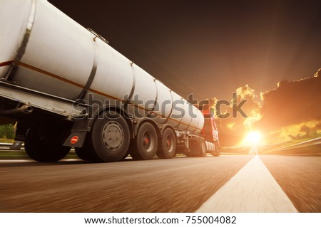 Big metal fuel tanker truck in motion shipping fuel against dark sky with sunset