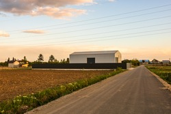Big metal industrial storage shed building.  Exterior of warehouse, no brands on storehouse with copy space.