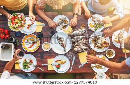 Big miltigeneration family dinner in process. Top view vertical image on table with food and hands  #1299574018