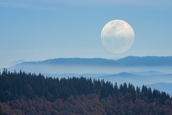 Big Moon rising above the distant mountains. Mosaic photo.
