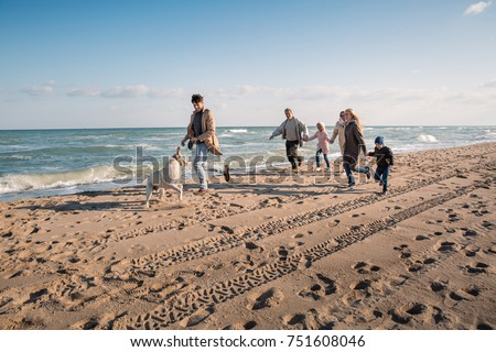 big multigenerational family running with labrador dog on beach at seaside