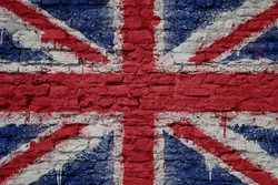 big national flag of great britain on a massive old brick wall
