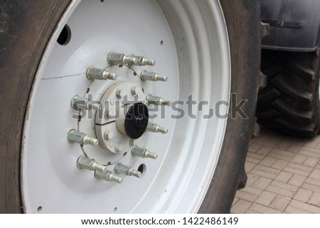 Big new tractor wheel with overlay threaded bolts on hub  for mounting dual wheels - agricultural machinery close up #1422486149