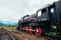 Big old dark steam train with red wheels has arrived at the mountain station. Vintage and nostalgic impressive passenger historic steam machine. Translation: