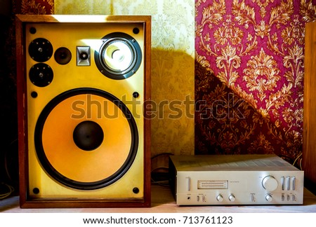 big old open speaker with small round Loudspeaker and black keys. Musical column with yellow body as a source of pure sound in sunshine against red and yellow wall #713761123